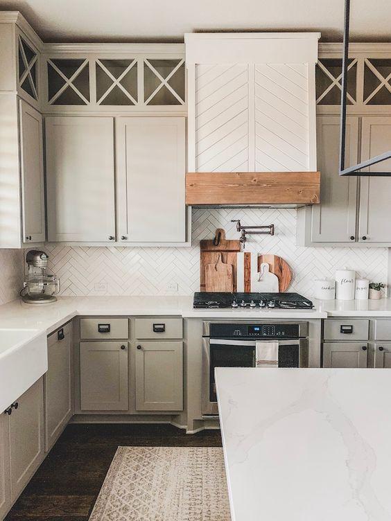 a dove grey kitchen with a white herringbone tile backsplash, a matching hood, white quartz countertops and black fixtures