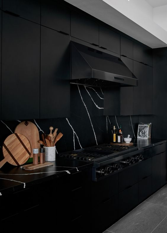 a dramatic black kitchen with black marble countertops and a backsplash, with a black hood and appliances is very elegant