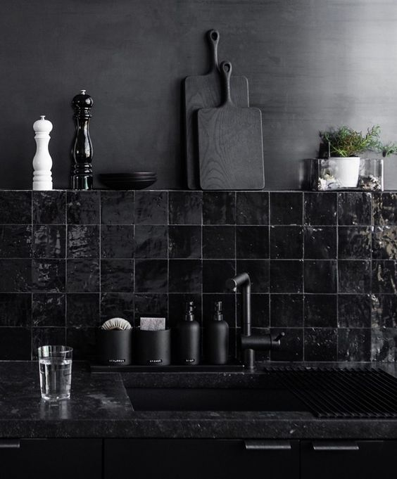 a dramatic black kitchen with black quartz countertops, a black glossy tile backsplash and a matte black wall is very cool