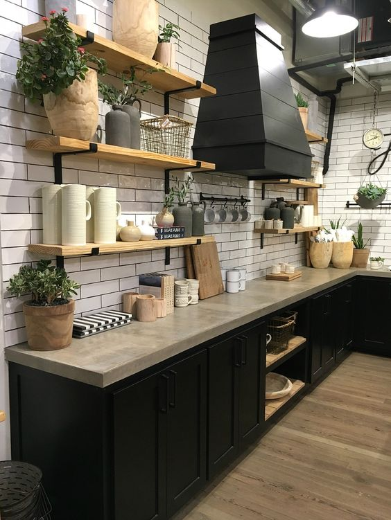a farmhouse black kitchen with concrete countertops, a white skinny tile backsplash and light stained open shelves