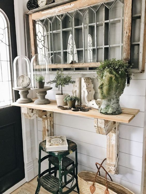a farmhouse console with a head-shaped planter, greenery in pots and a clock in a cloche