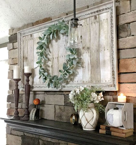 a farmhouse mantel with a greenery wreath, greenery and white blooms in a jug, candles in wooden candleholders