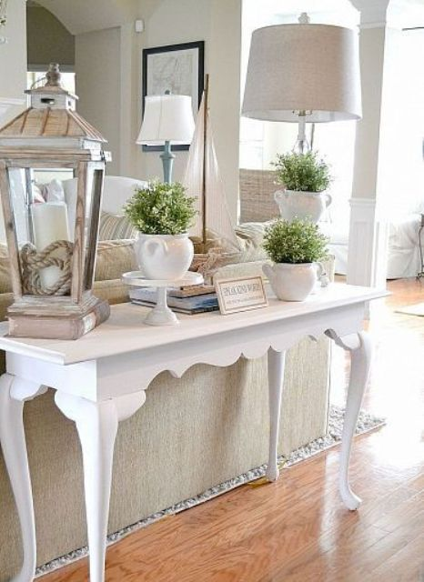 a farmhouse spring console table with a candle lantern, greenery in sugar pots and a vintage lamp is a stylish idea