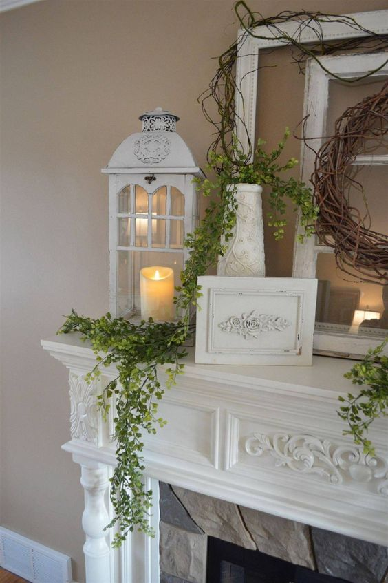 a farmhouse spring mantel with greenery, a vine wreath, a candle lantern looks fresh, elegant and pretty