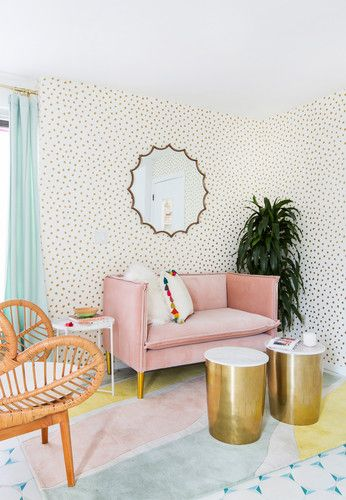 a fun and bold room with creative mid-century modern wallpaper, a pink loveseat, gilded tables and a rattan chair
