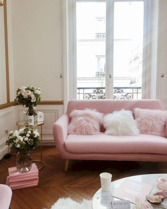 a girlish living room with a pink loveseat, pink fluffy pillows, blooms and pink accessories is very cute and chic