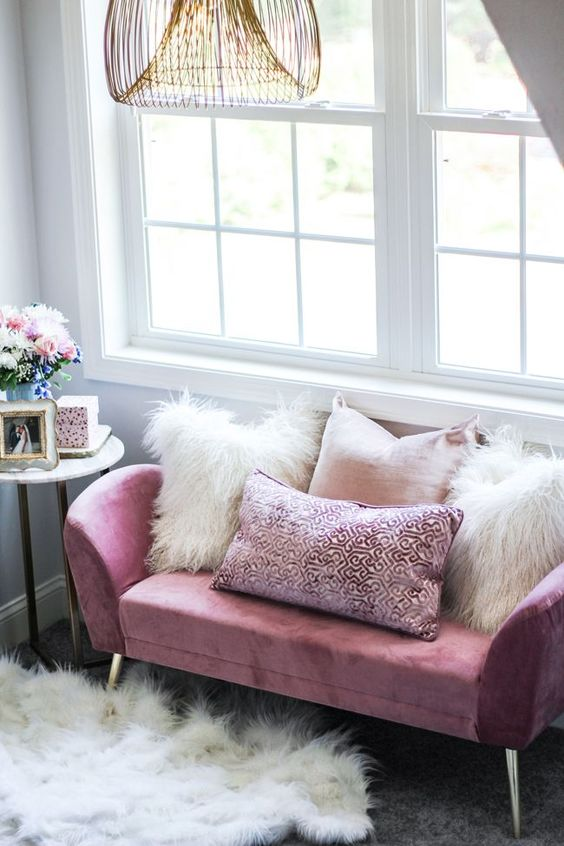a glam girlish look with a pink loveseat and pink and white fur pillows, a faux fur rug and a catchy chandelier