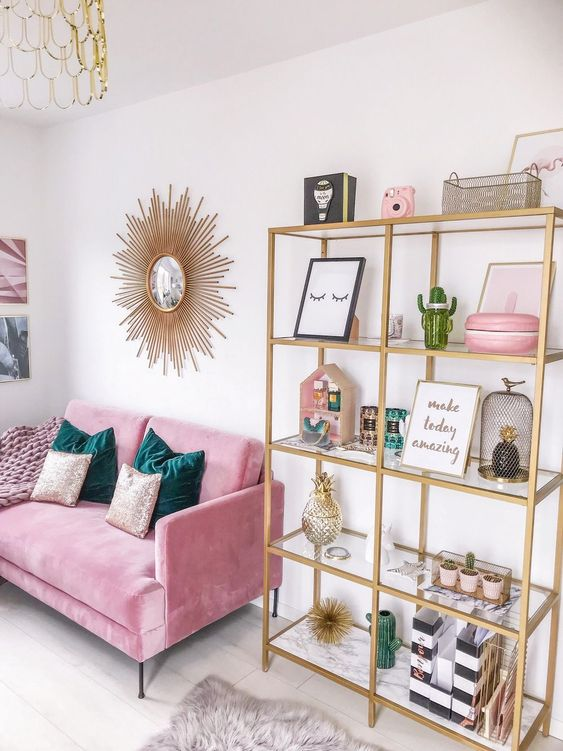 a glam room with a gold glass storage unit, a pink loveseat, a gold burst mirror and green and sequin pillows
