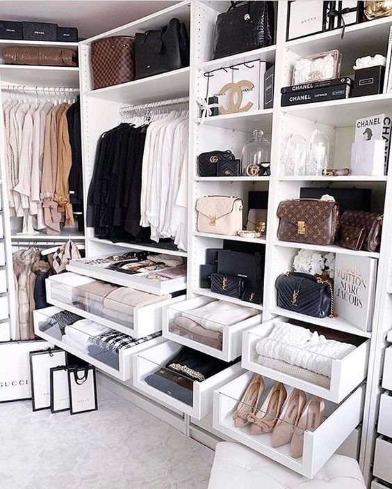 a glam walk-in closet done in white with many open storage compartments for everything, clear drawers to see what's inside and boxes for storage