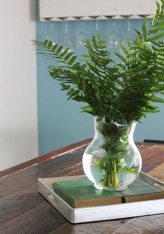 a glass vase with ferns placed on books and a tray is a simple and casual idea for spring