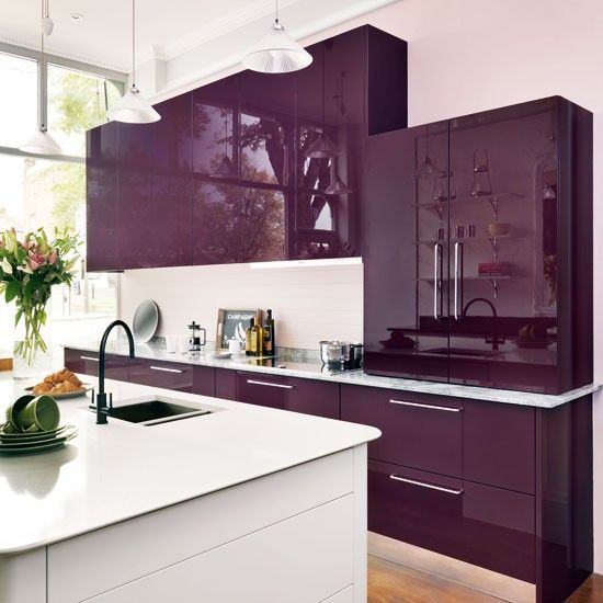 a glossy plum contemporary kitchen with a white countertop and backsplash, a white kitchen island and pendant lamps