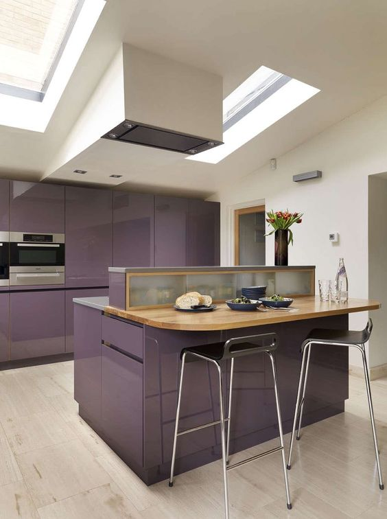 a glossy purple kitchen with stone and butcherblock countertops, a hood and skylights is very stylish