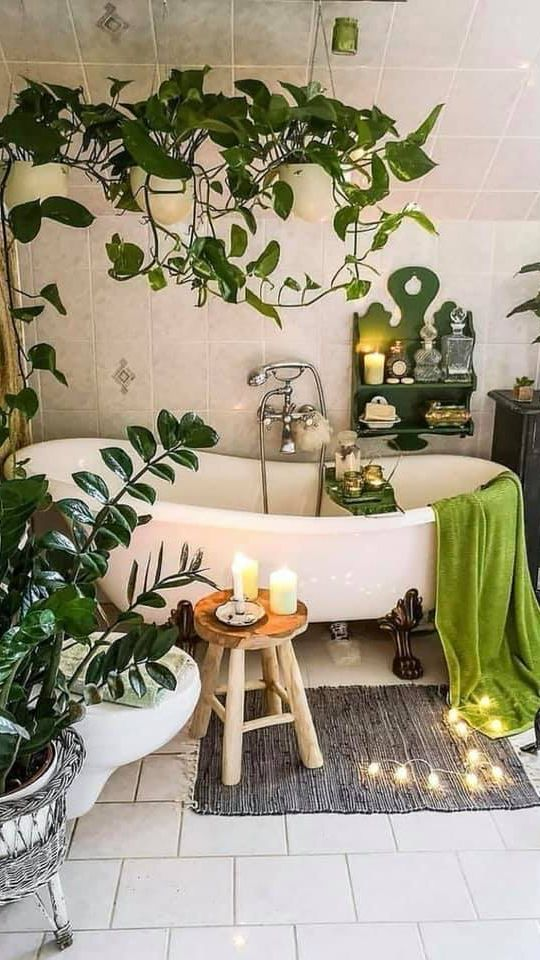 a gorgeous bathroom with a clawfoot tub, some statement plants and indoor vines, green towels and a shelf