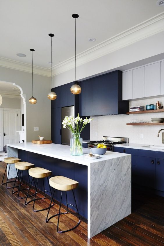 a gorgeous navy and white kitchen with a white stone waterfall countertop and pendant lamps plus wooden stools