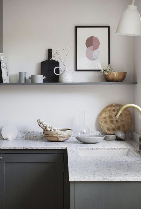 a graphite grey kitchen with light grey terrazzo countertops and a long shelf instead of upper cabinets for an airy feel in the space