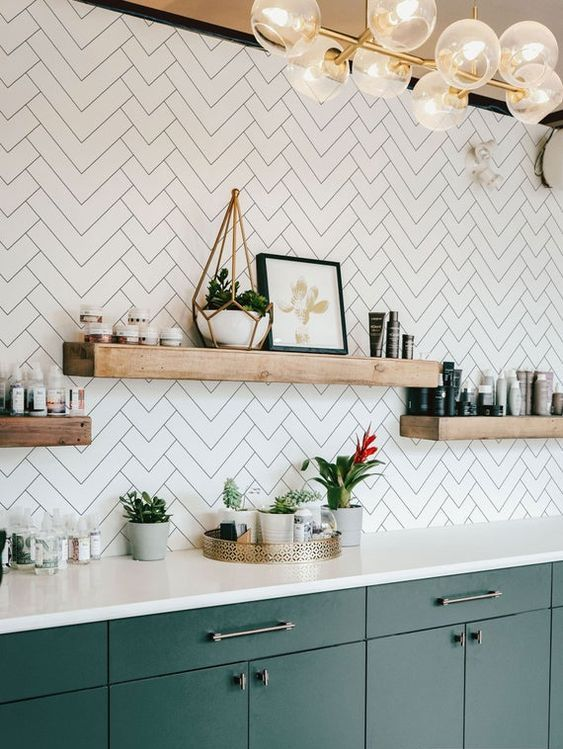 a green kitchen with white countertops and a white herringbone backsplash plus floating shelves looks catchy