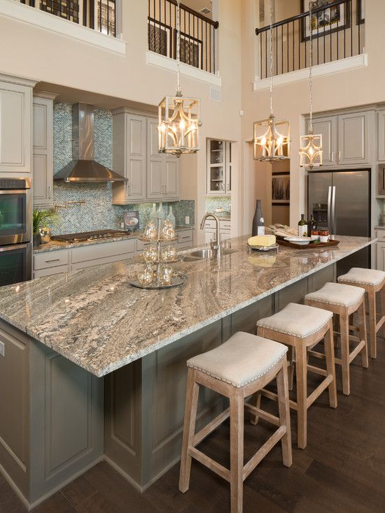 a grey and tan vintage kitchen with grey granite countertops, a blue tile backsplash, vintage pendant lamps that highlight a double height ceiling