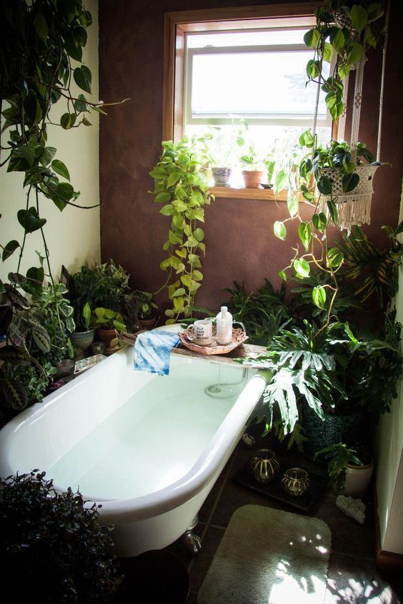 a home space in boho style, with lots of potted greenery and climbing plants, a bathtub and candles is cool