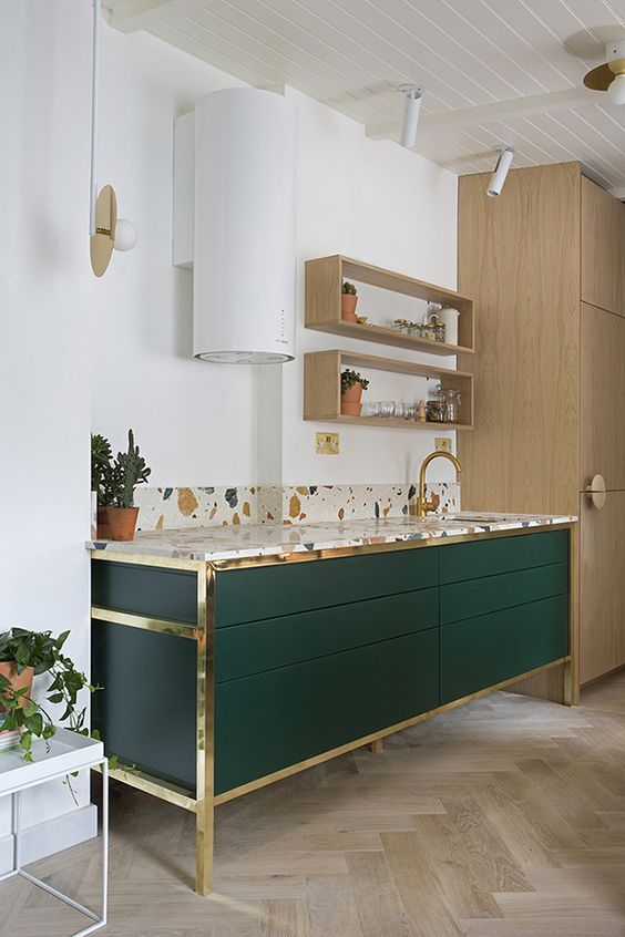 a hunter green kitchen island with gold touches and a bright terrazzo countertop and a backsplash looks very chic and bold