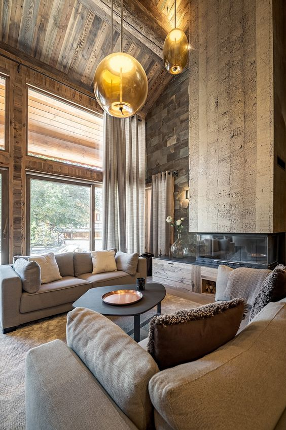 a jaw-dropping chalet living room with all wood around, a stone wall, a catchy fireplace, modern furniture and hanging lamps