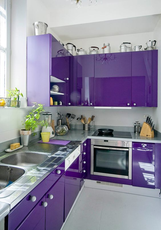 a jaw-dropping glossy purple kitchen with grey stone countertops and white knobs is a very bold and eye-catchy space