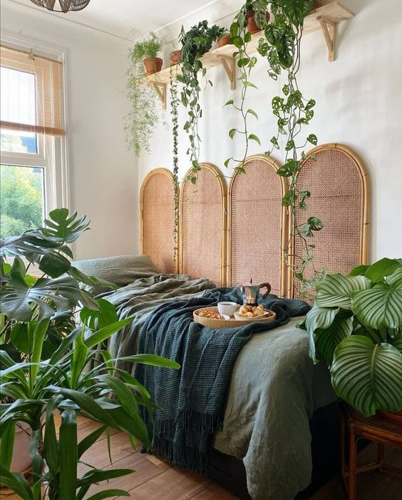 a jungle-themed bedroom with a rattan screen, green bedding, statement potted plants and climbing ones