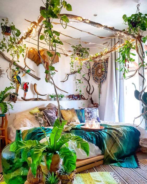 a jungle-themed bedroom with a stick canopy with lights and climbing plants, bright bedding, potted plants and faux taxidermy