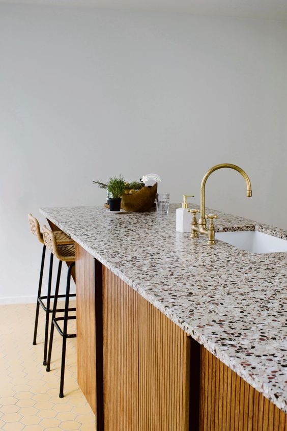 a kitchen island with rather a neutral yet stylish countertop, a gold faucet and some rattan stools is very elegant and chic