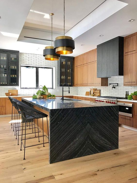a large black and stained kitchen with a white subway tile backsplash and a kitchen island with a black waterfall countertop that inspires