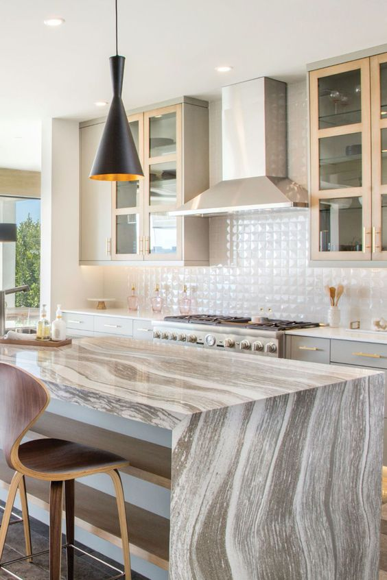 a light grey kitchen with stained touches, a white tile backsplash, bras touches, a statement grey quartz kitchen island and a black pendant lamp