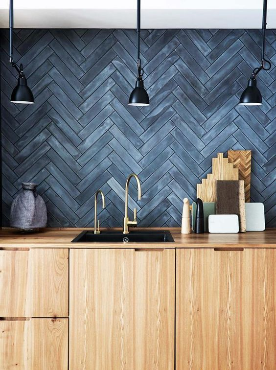 a ligth stained wooden kitchen with a slate grey herringbone backsplash and vintage black lamps over the space