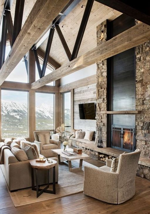 a lodge living room with a faux stone wall with a fireplace, neutral furniture and glazed walls plus wooden beams