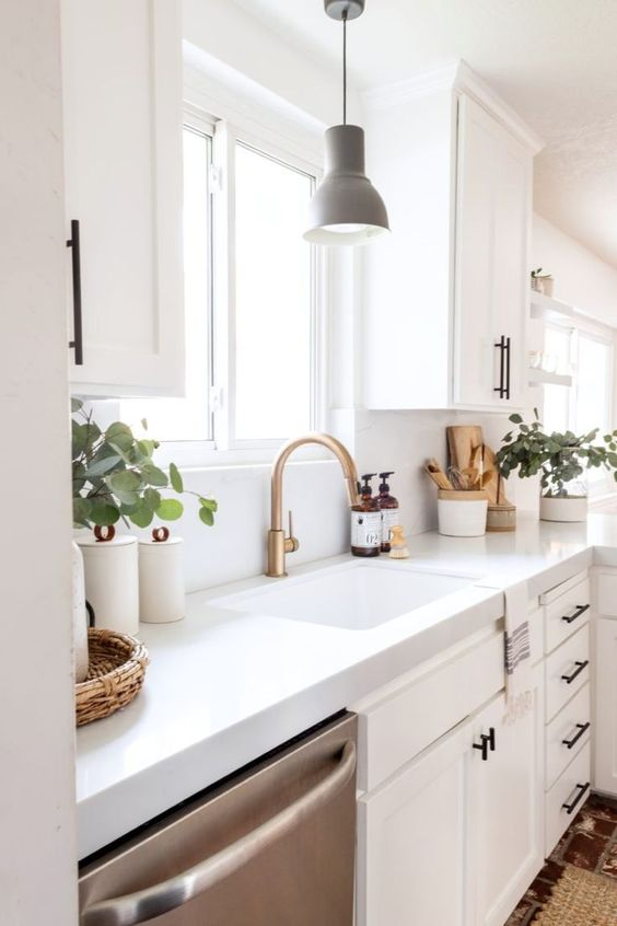 a lovely all-white kitchen with vintage cabinets and white quartz countertops, brass touches and a grey pendant lamp plus potted greenery