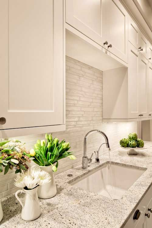 a lovely creamy kitchen with a white tile backsplash and a white granite countertop plus modern fixtures is a cool space