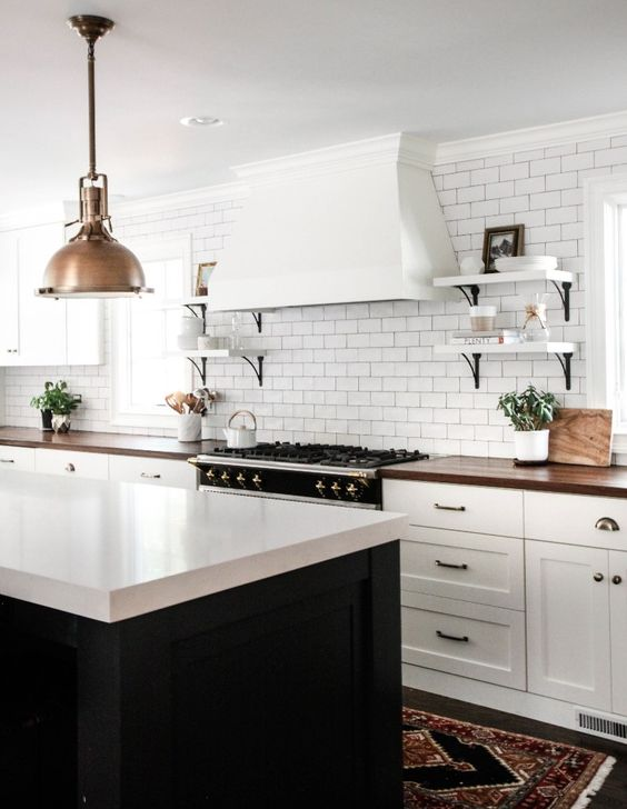 a lovely farmhouse kitchen with white cabinets and a black kitchen island, butcherblock countertops and a quartz one on the island plus a white tile backsplash