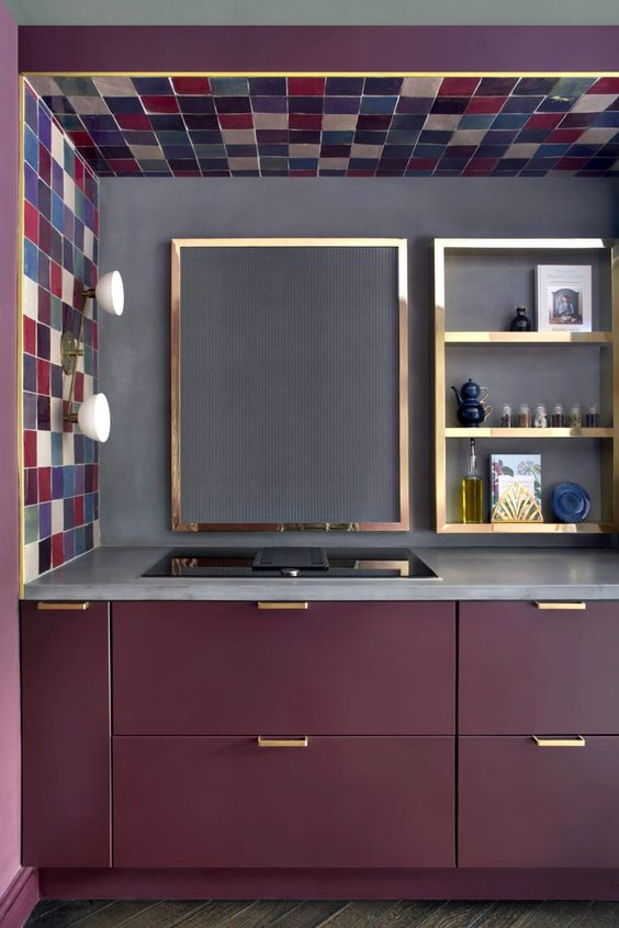 a lovely matte purple kitchen with a concrete countertop and backsplash plus gold frames and gold handles