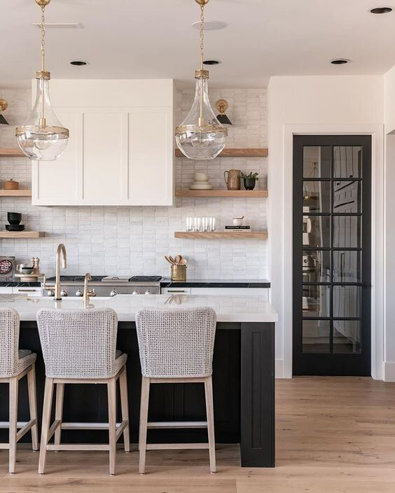 a lovely modern ktichen with white cabinets and a black kitchen island, white quartz countertops, brass fixtures and glass pendant lamps