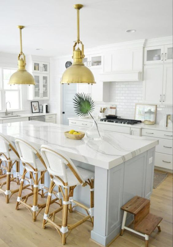 a lovely tropical kitchen with white cabinets and a light blue kitchen island, white quartz countertops and rattan stools plus pendant lamps