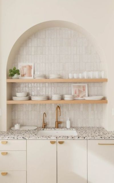 a lovely warm neutral kitchen with a cool terrazzo countertop and a skinny tile backsplash plus open shelves in a niche is cool