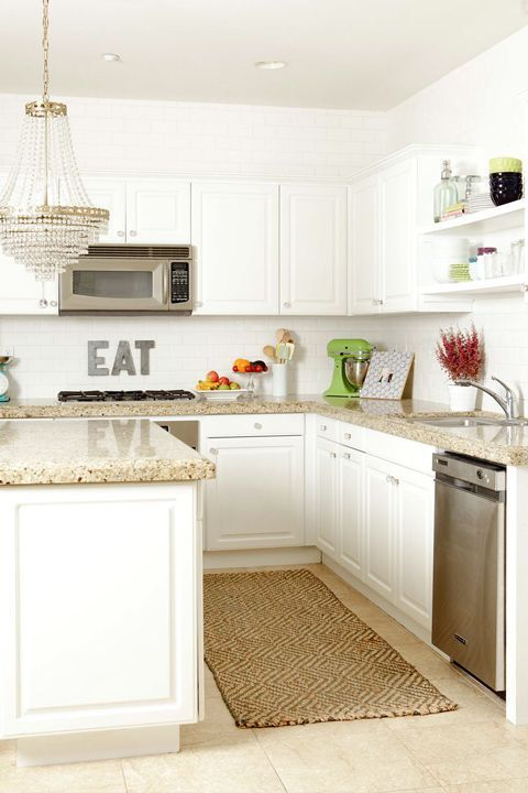 a lovely white kitchen with grey granite countertops, a white tile backsplash and a refined crystal chandelier