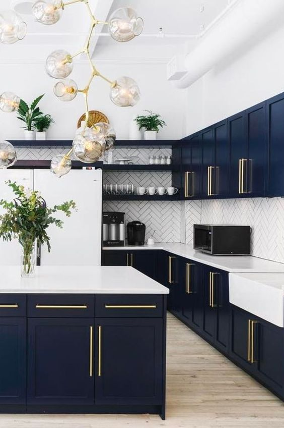 a luxurious navy kitchen with a white herringbone tile backsplash and quartz countertops, brass handles and an eye-catchy bubble chandelier