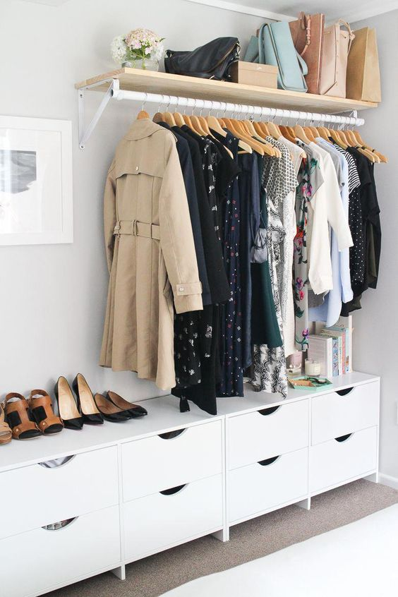 a makeshift closet with a shelf for bags and a long dresser for smaller things and accessories used for shoes, too