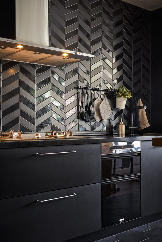 a metal black kitchen with black quartz countertops, a black herringbone backsplash with glossy and matte touches