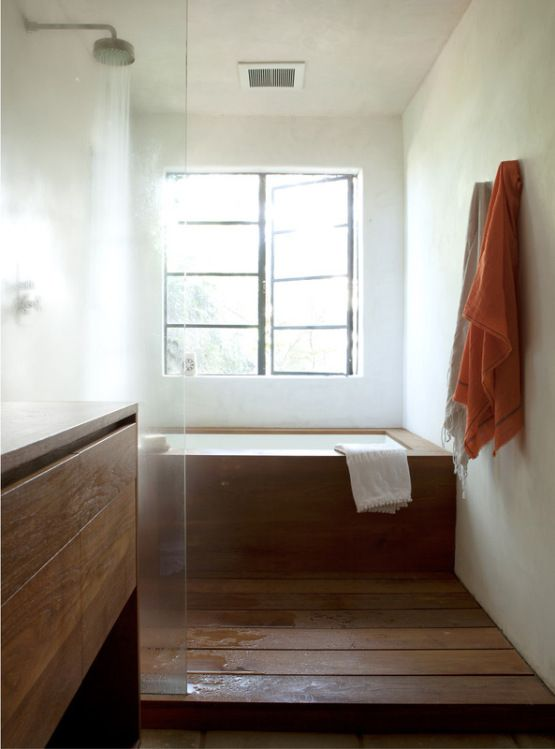 a mid-century modern bathroom in neutrals, with a wooden floor, vanity and a bathtub clad with wood is inviting