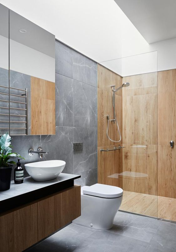 a minimalist bathroom clad with grey stone, with wood in the shower space and a floating wooden vanity
