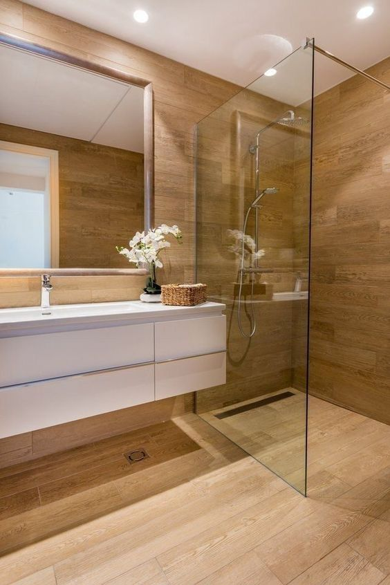 a minimalist bathroom completely clad with wood, with a white floating vanity and built-in lights is chic