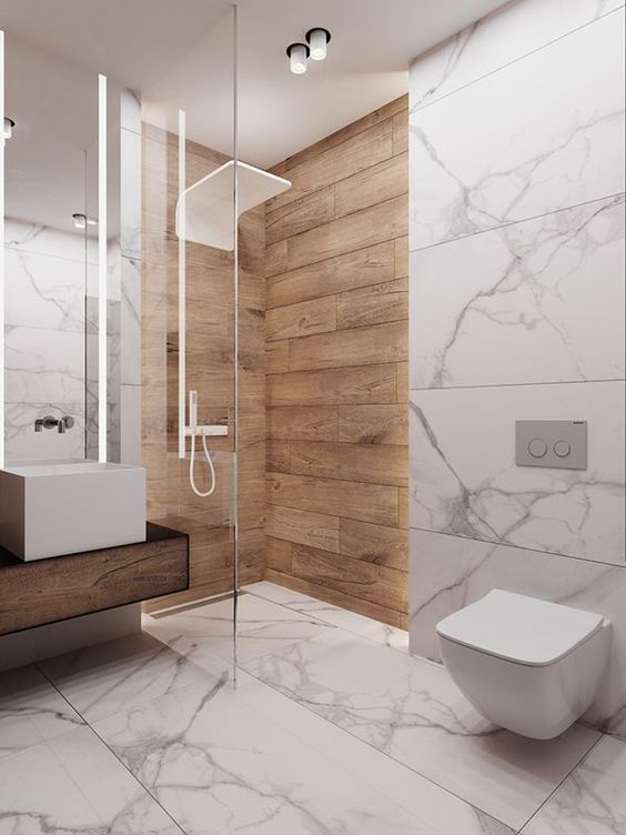 a minimalist bathroom done with marble tiles, with wood tiles in the shower and a wooden floating vanity is chic
