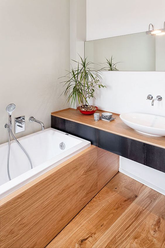 a minimalist bathroom with a wooden vanity, floor and a bathtub clad with wood is a stylish space