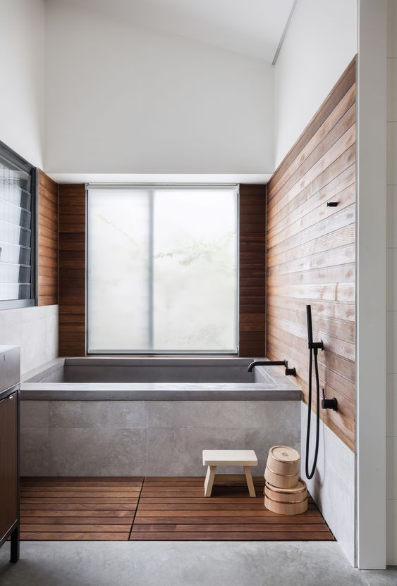 a minimalist bathroom with wooden walls and a floor, a bathtub clad with tiles and black fixtures