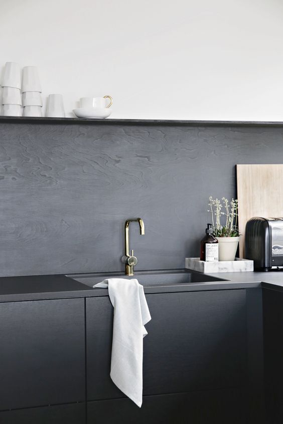 a minimalist black kitchen with sleek cabinets, a black veneer backsplash and concrete countertops plus touches of gold